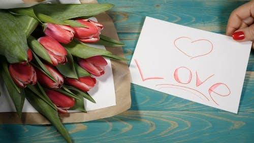 Draufsicht auf eine Liebesbotschaft Notiz und Tulpen Blumen Blumenstrauß auf einem Holztisch Liebesbeziehung