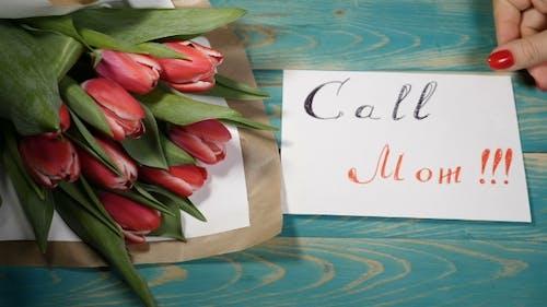 Rufen Sie Mom Nachricht Notiz und Tulpen Blumen Bouquet auf einem Holztisch. Liebesbeziehung