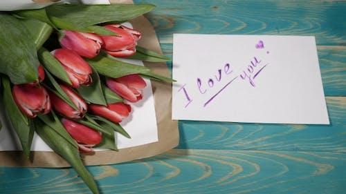 I Need You Nachricht Notiz und Tulpen Blumen Blumenstrauß auf einem Holztisch Liebe