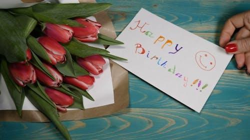 Happy Birthday Nachricht Hinweis und Tulpen Blumen Blumenstrauß auf einem Holztisch Liebe