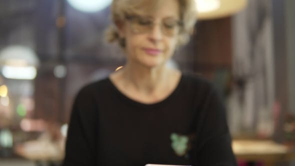 Thumbnail for A Middle-aged Woman Uses Mobile Phones in a Cafe
