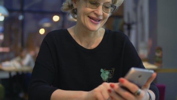 A Middle-aged Woman Uses Mobile Phones in a Cafe