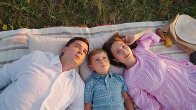 Happy Family Lying on Ground and Looking Up in the Sky