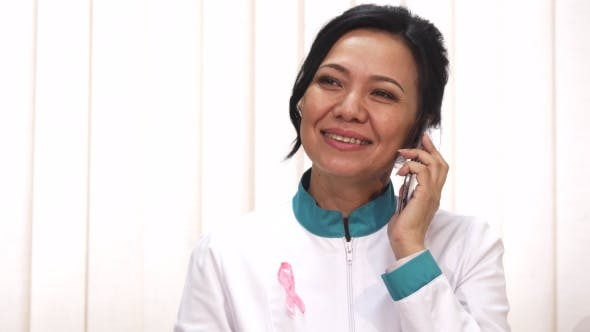 Thumbnail for Beautiful Asian Mature Female Doctor Talking on the Phone Smiling Joyfully