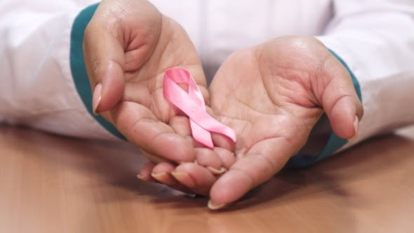 Thumbnail for Female Doctor Holding Pink Ribbon for Breast Cancer Awareness