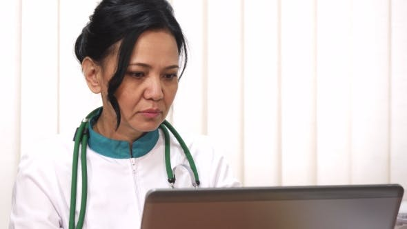 Thumbnail for Beautiful Asian Female Mature Doctor Working on Her Laptop
