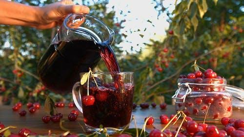 Cherry Juice on Background of Growing Cherries