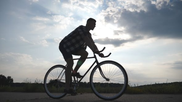 Thumbnail for Silhouette of Man Riding at Vintage Bicycle with Beautiful Sunset Sky at Background