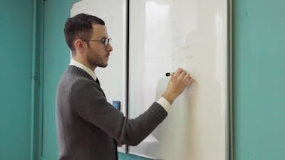 Man Teacher Writes on White Board in Class Room