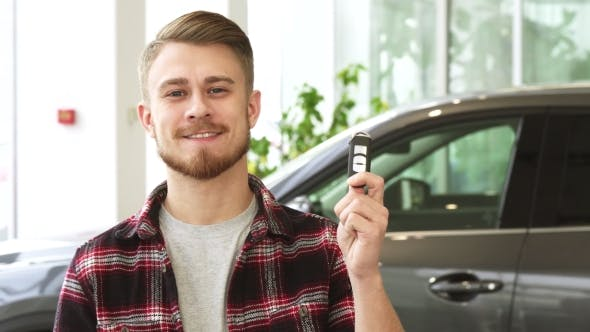 Thumbnail for Attractive Young Man Smiling Holding Car Keys Posing at the Automotive Dealership