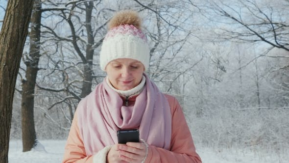 Cover Image for Young Woman Walks in Winter Park, Enjoys Smartphone