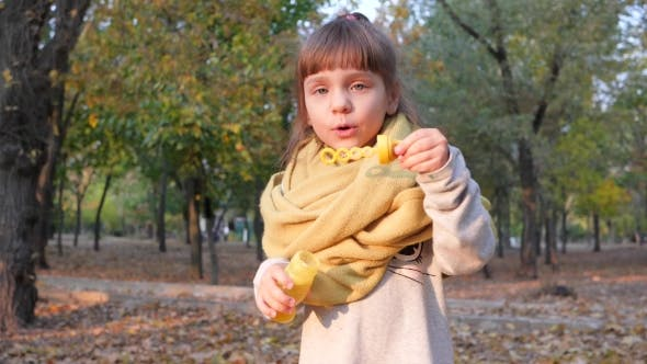 Cover Image for Portrait of a Cute Kid Blowing Soap Bubbles and Smiling in Autumn Park