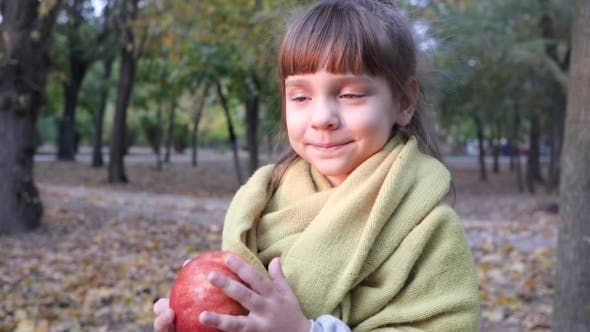 Thumbnail for Handsome Little Girl Trying To Eat Big Red Apple in the Open Air in Autumn Park