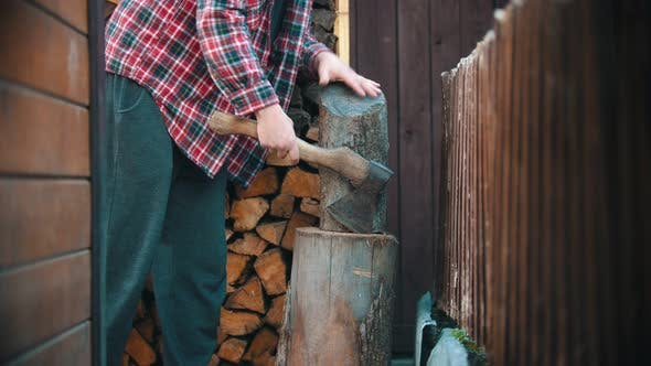 Woodcutter About To Chop Big Log with an Ax in Woodpile