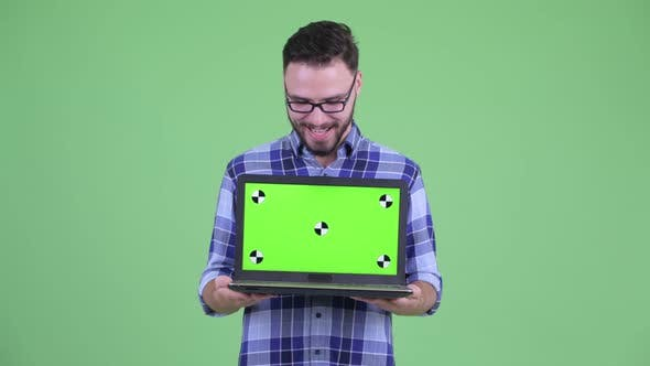 Cover Image for Happy Young Bearded Hipster Man Showing Laptop and Looking Surprised
