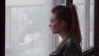 Unhappy Young Woman Looks Out the Window
