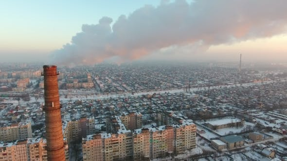 Thumbnail for Aerial Shot of an Incredibly High Tower with Slow Smoke at Sunset in Winter