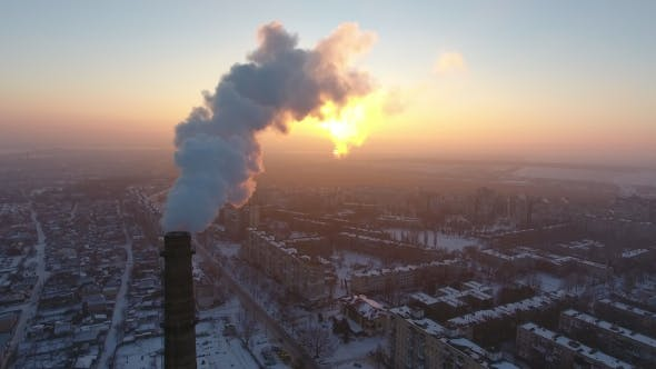 Thumbnail for Aerial Shot of a Sky High Chimney with Slow White Smoke at Sunset in Winter