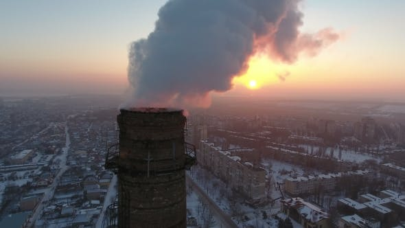 Thumbnail for Aerial  Shot of a Big Industrial Tower with White Smoke at Sunset in Winter