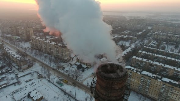 Thumbnail for Aerial  Shot of a High Industrial Pipe with White Smog at Sunset in Winter
