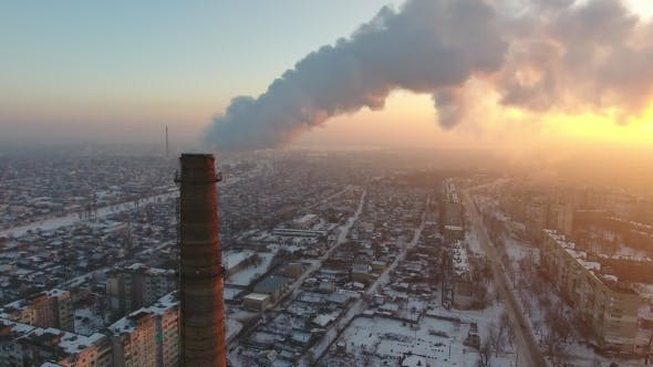 Thumbnail for Aerial Shot of a Giant Chimney with Slow White Smoke at Sunset in Winter