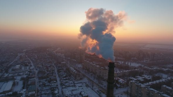 Thumbnail for Aerial Shot of a Colossal Industrial Tower with Thick Smoke at Sunset in Winter