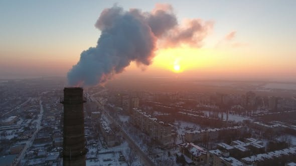 Thumbnail for Aerial Shot of an Elevated Industrial Tower with Heavy Smoke at Sunset in Winter