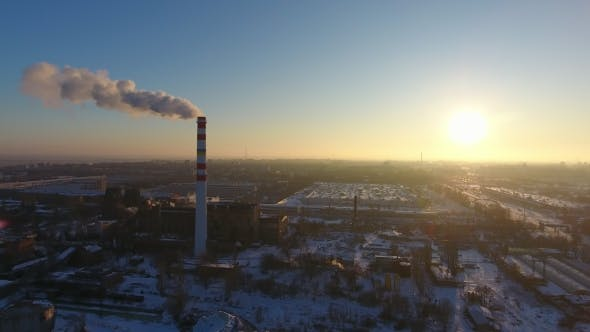 Thumbnail for Aerial Shot of an Elevated Hot Gas Chimney with Dark Smoke at Sunset in Winter
