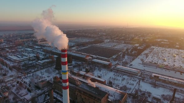 Thumbnail for Aerial Shot of a High White and Red Tower with White Smoke at Sunset in Winter