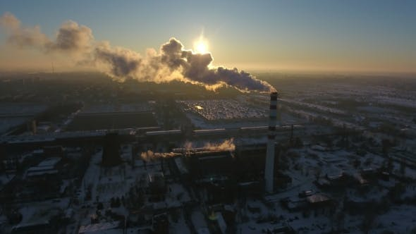 Thumbnail for Aerial Shot of a Soaring Brick Tower with White Smoke at a Nice Sunset in Winter