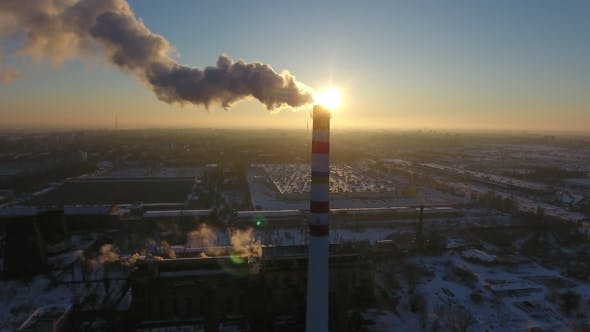 Thumbnail for Aerial Shot of a White and Red  Chimney with White Smoke at Sunset in Winter