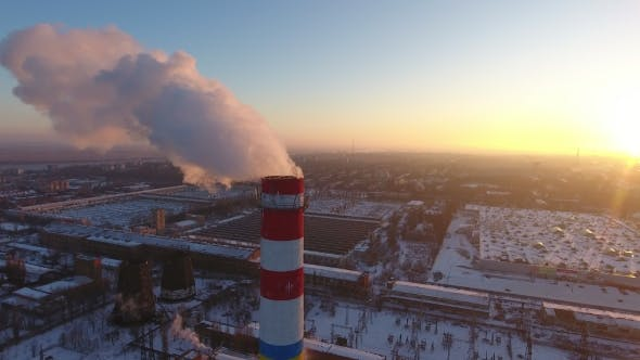 Thumbnail for Aerial  of a Gigantic Cooling Tower with White Smoke at Sunset in Winter