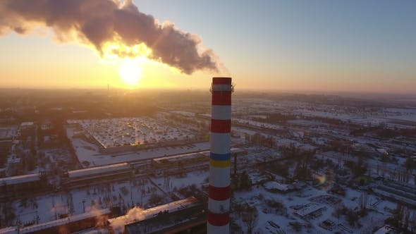 Thumbnail for Aerial Shot of a Sky-high Boiler Tower with White Smoke at Sunset in Winter