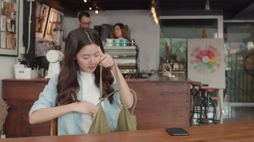 Cheerful Young Asian freelance lady working on laptop at coffee shop.
