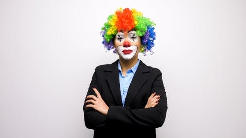 Clown with a Colorful Wig in Business Suit