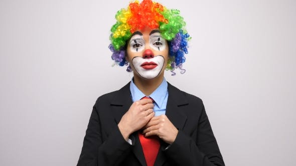 Conceptual Footage of Clown in Business Suit Arranging Her Tie