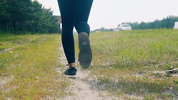 CU, Slow Motion, Low-angle Shot: Young Girl Goes in for Sports in the Morning, Runs Along a Pine