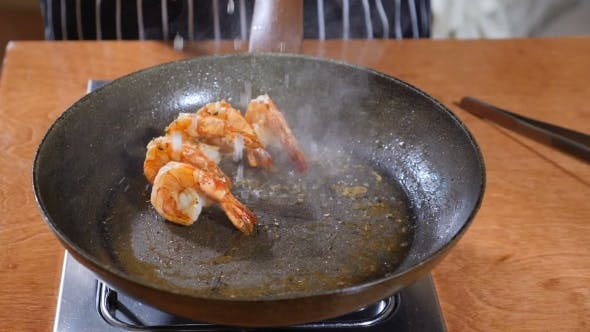 of a Chef Preparing Flambe Style Dish on a Pan Oil and Alcohol Ignite with Open Flames. Cooking