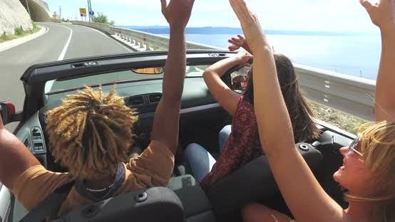 Thumbnail for Back view of friends waving arms driving on the coastal road in convertible