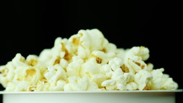 Thumbnail for A Glass of Popcorn on a Black Background. Slowly Rotates