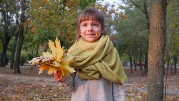 Thumbnail for Happy Little Female Smiling at Camera with Autumn Yellow Leaves in Hand in Park