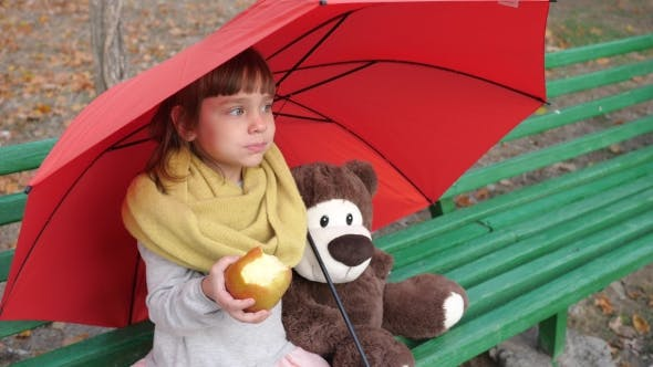 Cover Image for Lonely Little Girl Sits Near To Teddy Bear on Wooden Bench Under an Umbrella and Eats Red Apple on