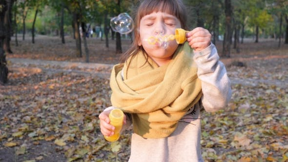 Cover Image for Pretty Kid Making Iridescent Soap Bubbles Into Camera Outdoors Autumn