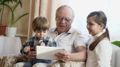Grandfather Using a Tablet Computer With Grandchildren
