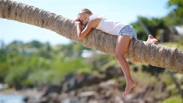 Thumbnail for Little Girl at Tropical Beach Sitting on Palm Tree During Summer Vacation