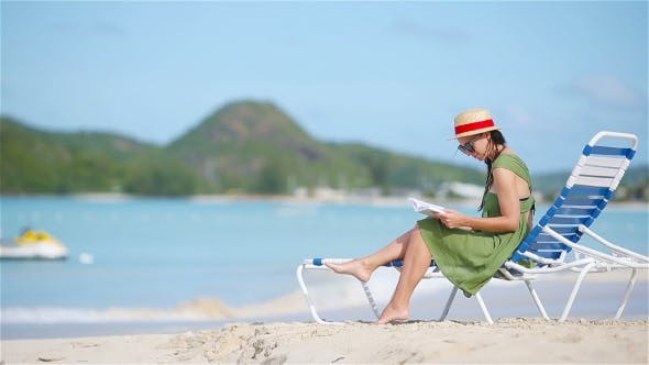 Thumbnail for Young Woman Reading Book on Sunbeds During Tropical White Beach