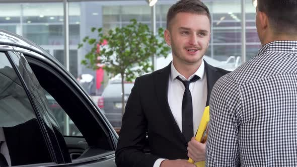 Cover Image for Car Dealer Shaking Hands with Male Customer After Selling an Automobile