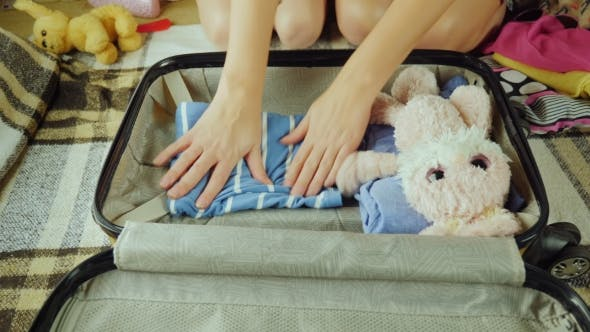 Thumbnail for A Woman with a Child Is Packing Things in a Suitcase for Traveling. They Put Clothes and Toys There