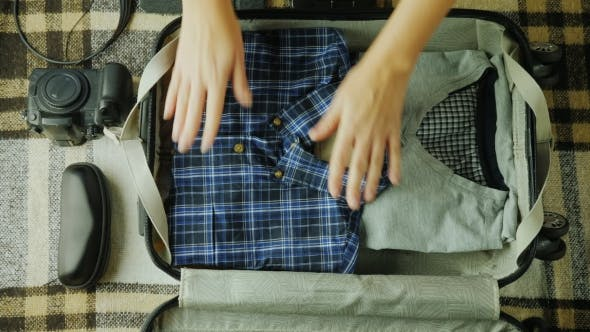 Cover Image for A Woman Is Packing a Suitcase. It Puts Things Together for Travel.