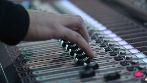 Thumbnail for Man Working at an Event Audio Mixer Knobs Being Pulled Hand Presses the Keys